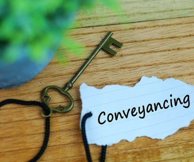 Key with a piece of paper that says conveyancing - property law